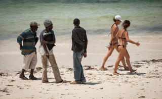 "Tourists walk past a group of ""beach boys"" in Malindi, Kenya. Photo by Mia Collis/PBS NewsHour"