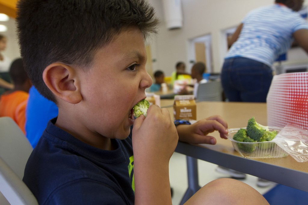 Six-year-old Jacob Portillo says he likes eating his broccoli at summer camp at Park View Recreation Center in downtown Washington. The camp offers free lunches to all the participants and to children in the community. The USDA pays for the summer meals. Photo by Margaret Myers/NewsHour