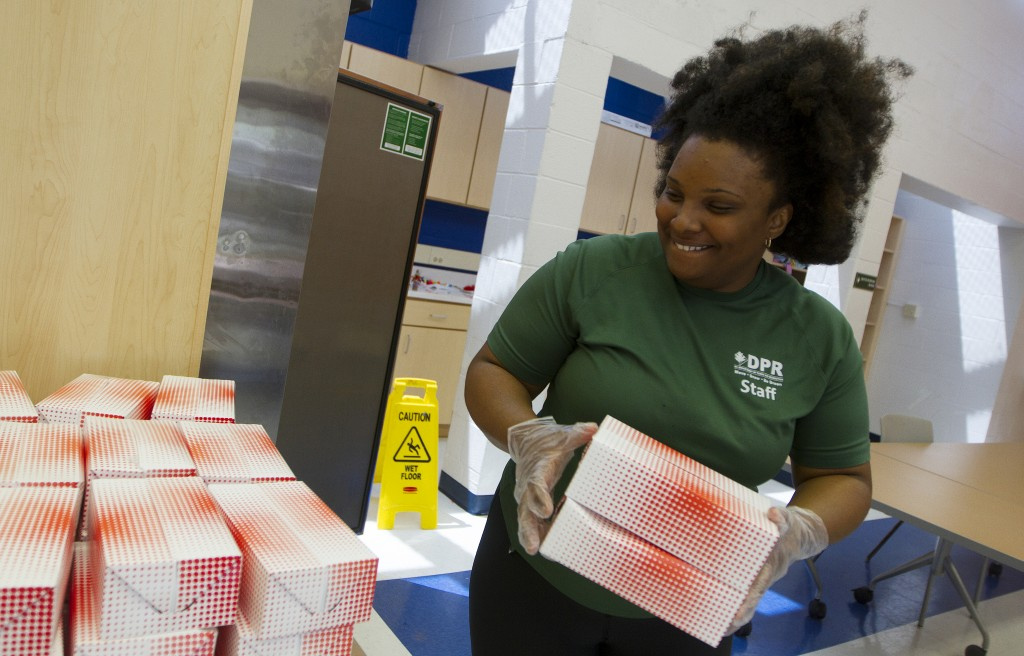Rec Specialist Michelle DeVille prepares the free boxed lunches at Park View Rec Center. Photo by Margaret Myers/NewsHour