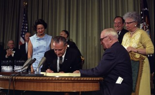 President Lyndon B. Johnson signing the Medicare Bill at the Harry S. Truman Library in Independence, Missouri. Former President Harry S. Truman is seated at the table with President Johnson. In the background from right to left: Senator Edward V. Long, an unidentified man, Lady Bird Johnson, Senator Mike Mansfield, Vice President Hubert Humphrey, and Bess Truman. Archive photo from the White House Press Office