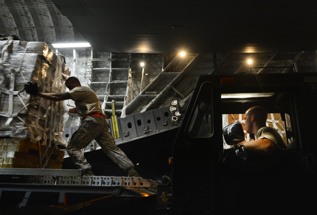 Staff Sgt. Daniel Leavindofske, 8th Expeditionary Air Mobility Squadron ramp team chief and Senior Airman David Babcock, air transportation journeyman, assist with loading 28,224 halal meals to a C-17 Globemaster III for a humanitarian airdrop mission over Iraq, Aug. 9, 2014. (U.S. Air Force photo by Staff Sgt. Vernon Young Jr.
