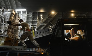 Staff Sgt. Daniel Leavindofske, 8th Expeditionary Air Mobility Squadron ramp team chief and Senior Airman David Babcock, air transportation journeyman, assist with loading 28,224 halal meals to a C-17 Globemaster III for a humanitarian airdrop mission over Iraq, Aug. 9, 2014. U.S. government handout photo courtesy of DVIC.