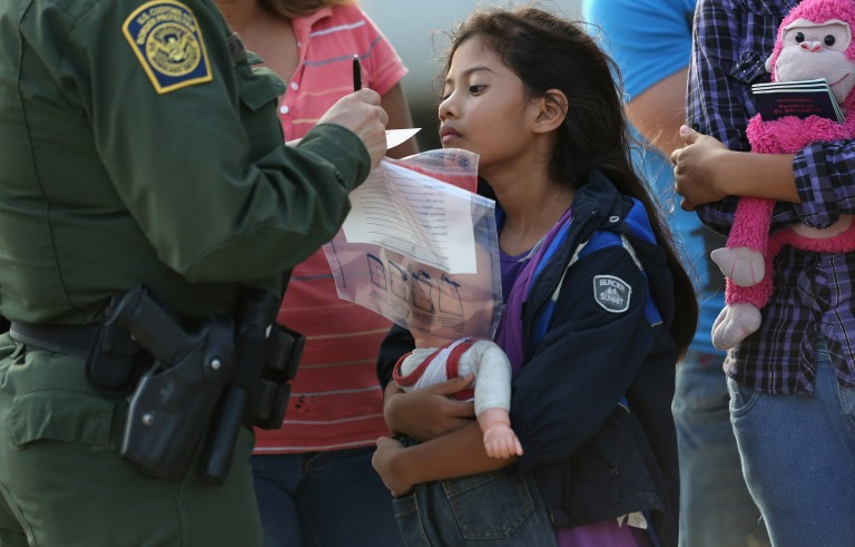 Salvadorian immigrant Stefany Marjorie, 8, watches as a U.S. Border Patrol agent records family information on July 24 in Mission, Texas. Photo by John Moore/Getty Images