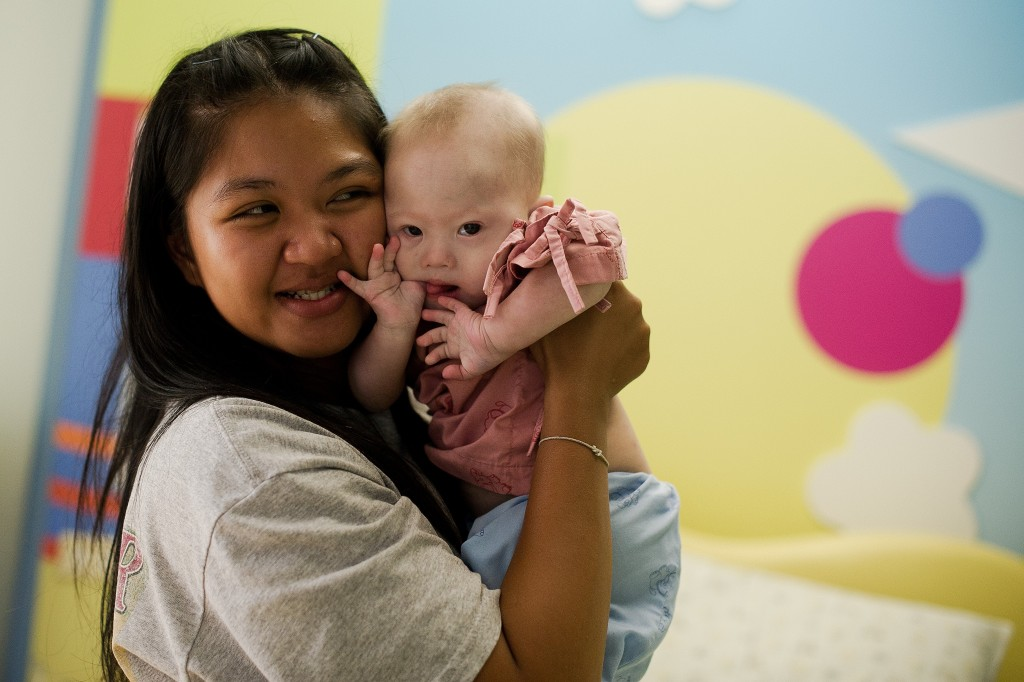 Thai surrogate mother Pattaramon Chanbua (L) holds her baby Gammy, born with Down Syndrome, at the Samitivej hospital, Sriracha district in Chonburi province on August 4, 2014. Photo by Nicolas Asfouri/Getty Images