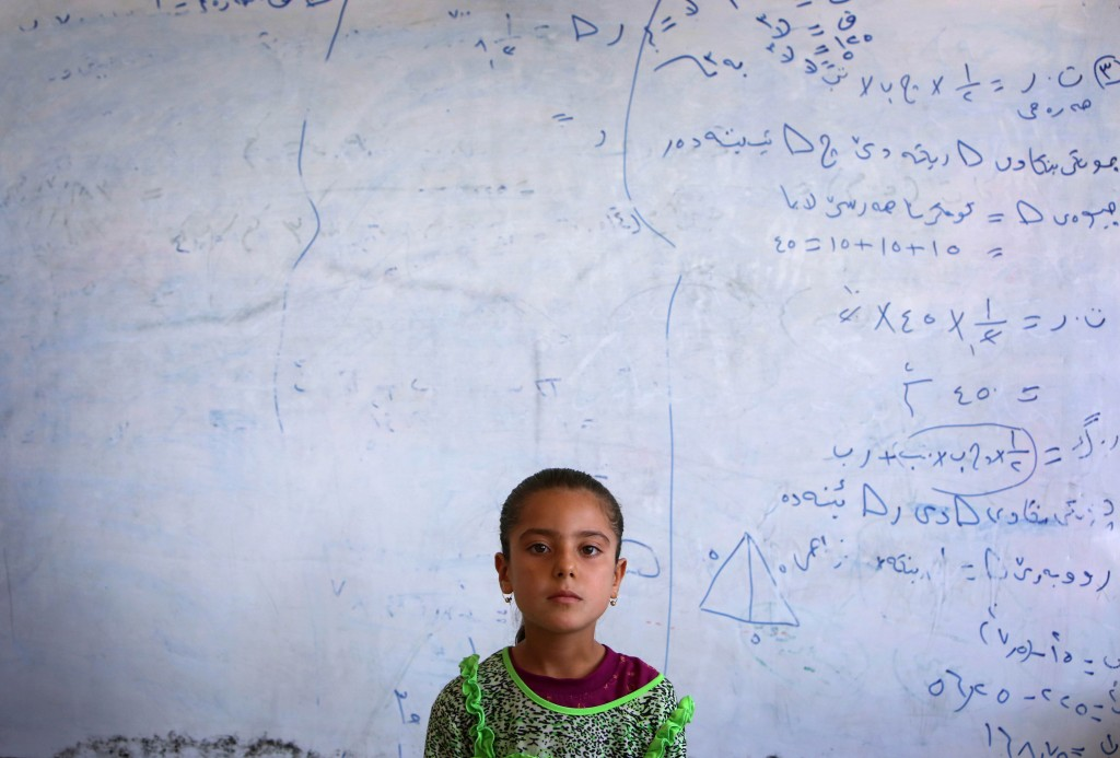 An Iraqi Yazidi girl who fled with her family the violence in the northern Iraqi town of Sinjar, stands at at a school where they are taking shelter in the Kurdish city of Dohuk in Iraq's autonomous Kurdistan region, on Aug 5. Photo by Safin Hamed/AFP/Getty Images