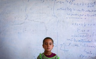 An Iraqi Yazidi girl who fled with her family the violence in the northern Iraqi town of Sinjar, stands at at a school where they are taking shelter in the Kurdish city of Dohuk in Iraq's autonomous Kurdistan region, on August 5, 2014. Photo by Safin Hamed/AFP/Getty Images