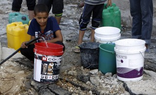 Palestinians fill containers with water from a broken main in Gaza City's al-Shejaea neighborhood on Aug. 6. Photo by Mohammed Abed/AFP/Getty Images