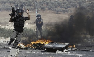 Israeli border guards clash with Palestinian protesters (unseen) following a demonstration in support of Gaza after Friday prayers at the Hawara checkpoint, east of the West Bank city of Nablus, on August 8, 2014. Israeli warplanes pounded targets across Gaza, where two Palestinians were killed and militants fired dozens of rockets into Israel after renewed hostilities ruptured a fledgling three-day truce. AFP PHOTO/ JAAFAR ASHTIYEH        (Photo credit should read MUSA AL-SHAER/AFP/Getty Images)