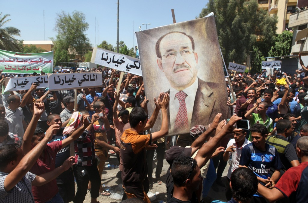 Iraqis hold a giant portrait of Iraq's Prime Minister Nuri al-Maliki during a demonstration to support him on Monday in Baghdad's central Saadoun Street after Maliki said he was filing a complaint against the president for violating the constitution. Maliki's Shiite coalition won April polls comfortably but his standing has been undermined by a jihadist offensive launched on June 9 that overran large swathes of Iraq. Photo by AMER AL-SAEDI/AFP/Getty Images
