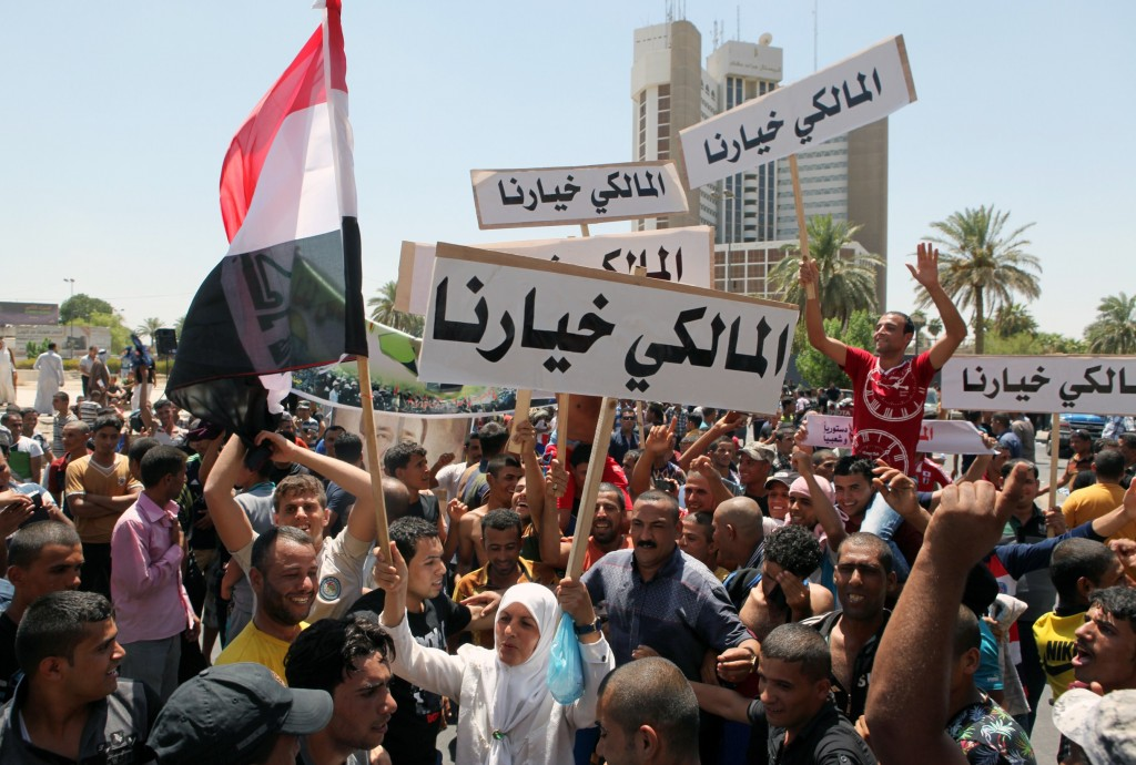 "Iraqis hold placards reading in Arabic ""Maliki is our choice"" during a demonstration to support Iraq's prime minister on August 11, 2014 in Baghdad's central Saadoun Street. Photo by Amer al-Saedi/AFP/Getty Images"