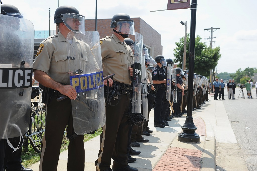 St. Louis County Law Enforcement Officers stand in riot gear during a protest of the shooting death of 18-year-old Michael Brown by a Ferguson police officer, outside Ferguson Police Department Headquarters August 11, 2014. Photo by Michael B. Thomas/Getty Images