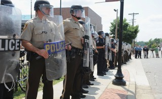 St. Louis County Law Enforcement Officers stand in riot gear during a protest of the shooting death of 18-year-old Michael Brown by a Ferguson police officer. Nearly two months later, an off-duty police officer fatally shot an 18-year-old black man Wednesday night in the St. Louis suburb of Shaw. Photo by Michael B. Thomas/Getty Images