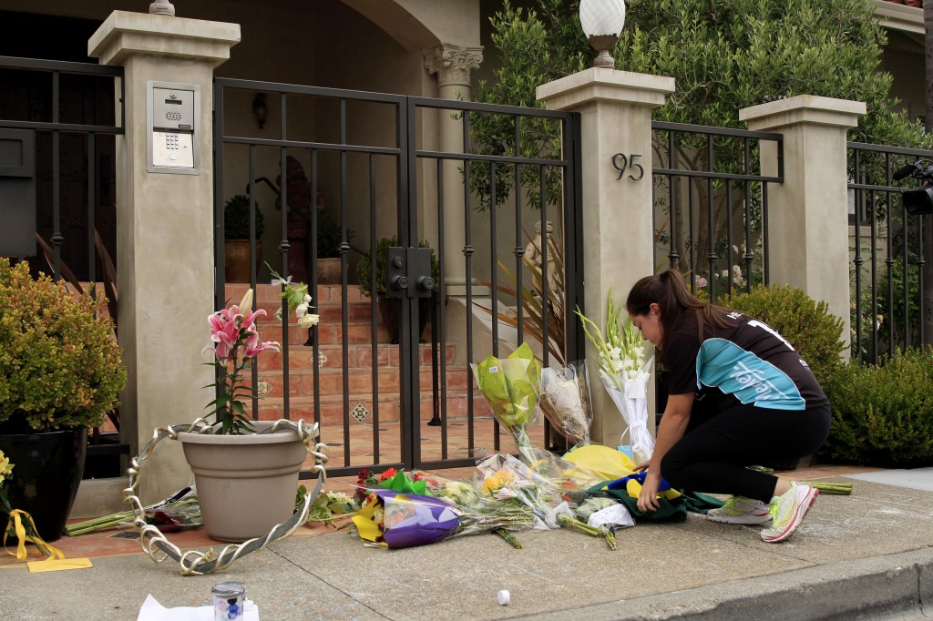 A fan places flowers in front of the home of actor and comedian Robin Williams in Tiburon, California, on Aug. 12. Williams committed suicide by hanging himself with a belt, local law enforcement said. Photo by Tayfun Coskun/Anadolu Agency/Getty Images