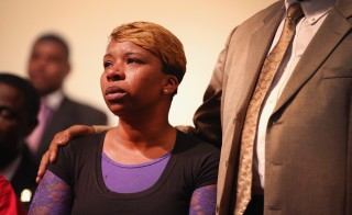 Tears roll down the cheek of Lesley McSpadden, the mother of slain teenager Michael Brown, during a community meeting held at Greater St. Marks Family Church in St Louis. Photo by Scott Olson/Getty Images