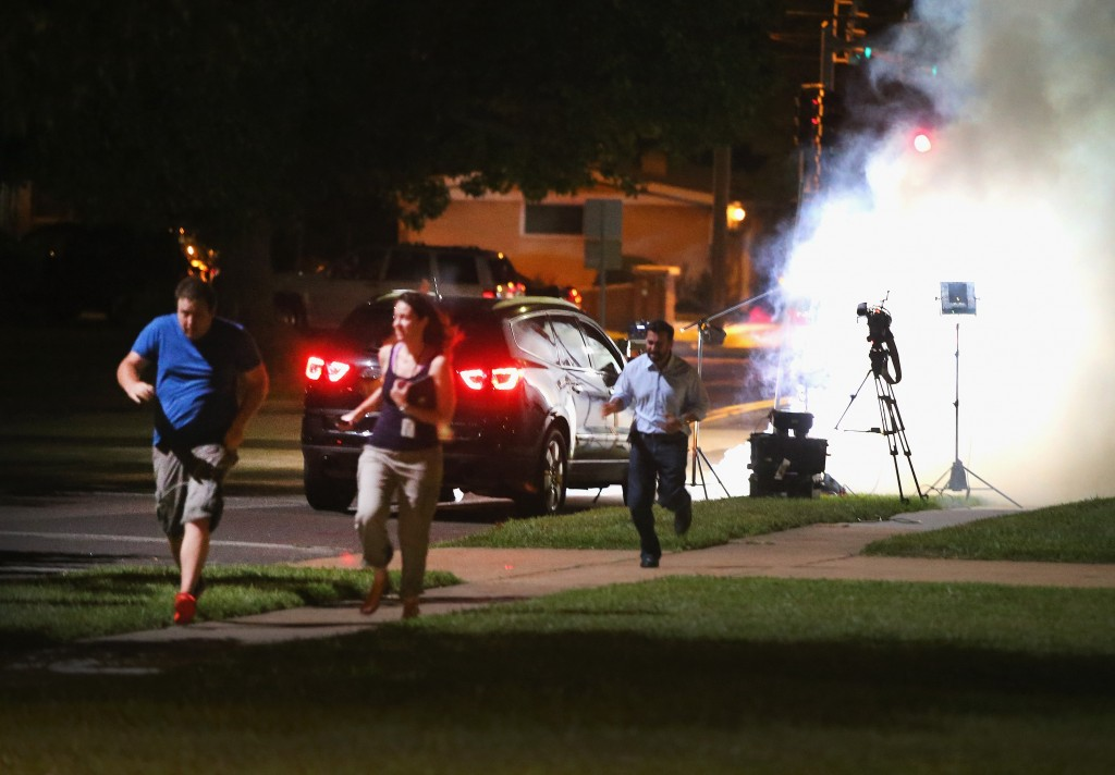 FERGUSON, MO - AUGUST 13: An Al Jazeera television crew, covering demonstrators protesting the shooting death of teenager Michael Brown, scramble for cover as police fire tear gas into their reporting position on August 13, 2014 in Ferguson, Missouri. Brown was shot and killed by a Ferguson police officer on Saturday. Ferguson, a St. Louis suburb, is experiencing its fourth day of violent protests since the killing. Photo by Scott Olson/Getty Images