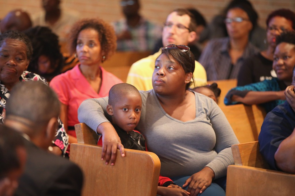 Caption:FERGUSON, MO - AUGUST 14: People listen as residents and faith and community leaders discuss unrest in the town of Ferguson following the shooting death of Michael Brown during a forum held at Christ the King UCC Church on August 14, 2014 in Florissant, Missouri. Seakers included Missouri Governor Jay Nixon and Senator Claire McCaskill (D-MO). Brown was shot and killed by a Ferguson police officer on August 9. Ferguson, a St. Louis suburb, has experienced four days of violent protests since the killing. (Photo by Scott Olson/Getty Images)