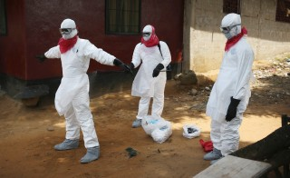 A Liberian health department burial team disinfects their protective clothing after retreiving the body of a woman suspected of dying of the Ebola virus on August 14, 2014 in Monrovia, Liberia. Photo by John Moore/Getty Images