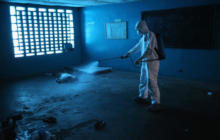 A Liberian health worker disinfects a corpse after the man died in a classroom now used as Ebola isolation ward on Aug. 15 in Monrovia, Liberia. With the right public health system in place, the countries in western Africa can contain and eradicate the the virus, writePhoto by John Moore/Getty Images
