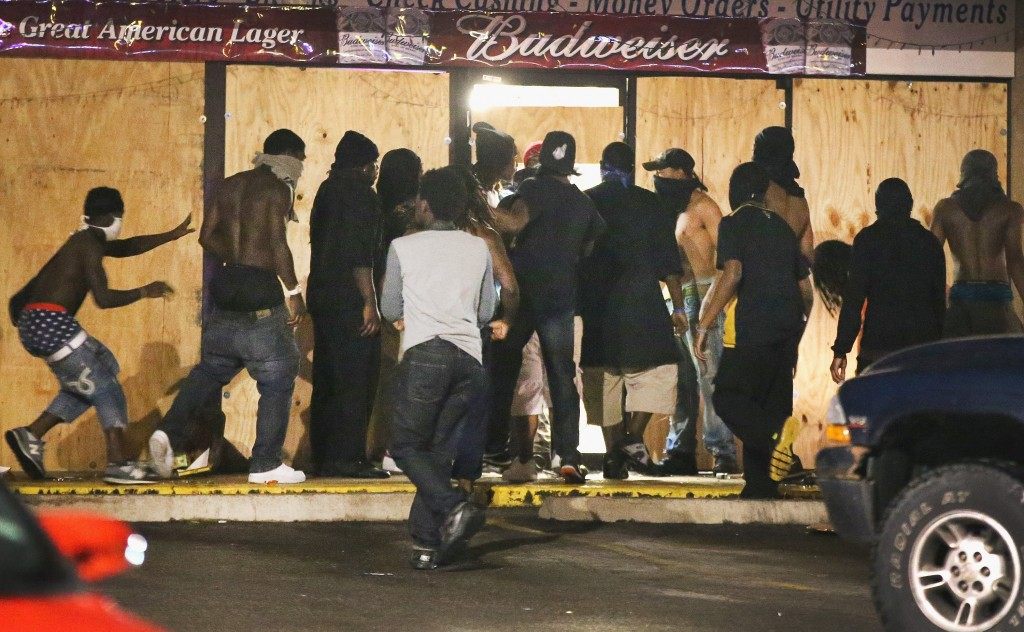 Protests in Ferguson, Missouri escalated into looting yesterday after police released information about Michael Brown's robbery and identified the officer who shot him.