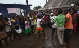 MONROVIA, LIBERIA - AUGUST 16: A family (C), leaves an Ebola isolation center after a mob forced open the gates of the facility in the West Point slum on August 16, 2014 in Monrovia, Liberia. A crowd of several hundred people, chanting, 'No Ebola in West Point,' opened the gates and took out the patients. Many in the crowd said that the Ebola epidemic is a hoax. The center, a closed primary school originally built by USAID, was being used by the Liberian Health Ministry to temporarily isolate people suspected of carrying the virus. Some 10 patients had 'escaped' the building the night before, according to a nurse there, as the center had no medicine to treat them. The Ebola epidemic has killed more than 1,000 people in four West African countries, with Liberia now having the most deaths. Photo by John Moore/Getty Images