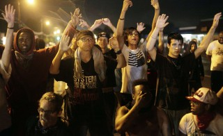 Demonstrators protest by holding their hands up while gathered on the streets of Ferguson, Missouri late on Aug. 16. A crowd of some 200 demonstrators defied a curfew that came into effect early on Aug. 17. Photo Joshua Lott/AFP/Getty Images