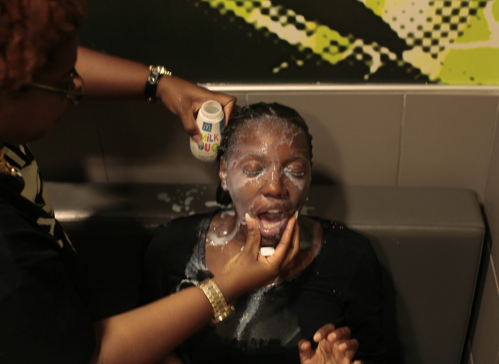 A woman has her face doused with milk after suffering the effects of what is reported to be tear gas used by police on Sunday in Ferguson, Missouri. Photo by Joshua Lott/Getty Images