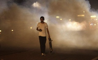 A man with a skateboard protesting Michael Brown's murder walks away from tear gas released by police Sunday in Ferguson, Missouri. Photo by Joshua Lott/Getty Images