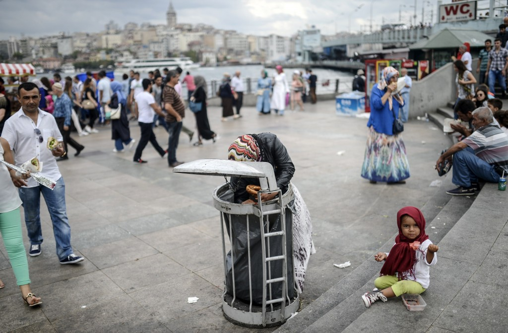 A Syrian refugee child eats food that her mother collected from a trash can at Eminonu Pier in Istanbul, Turkey on Aug. 18. Photo by Bulent Kilic/AFP/Getty Images