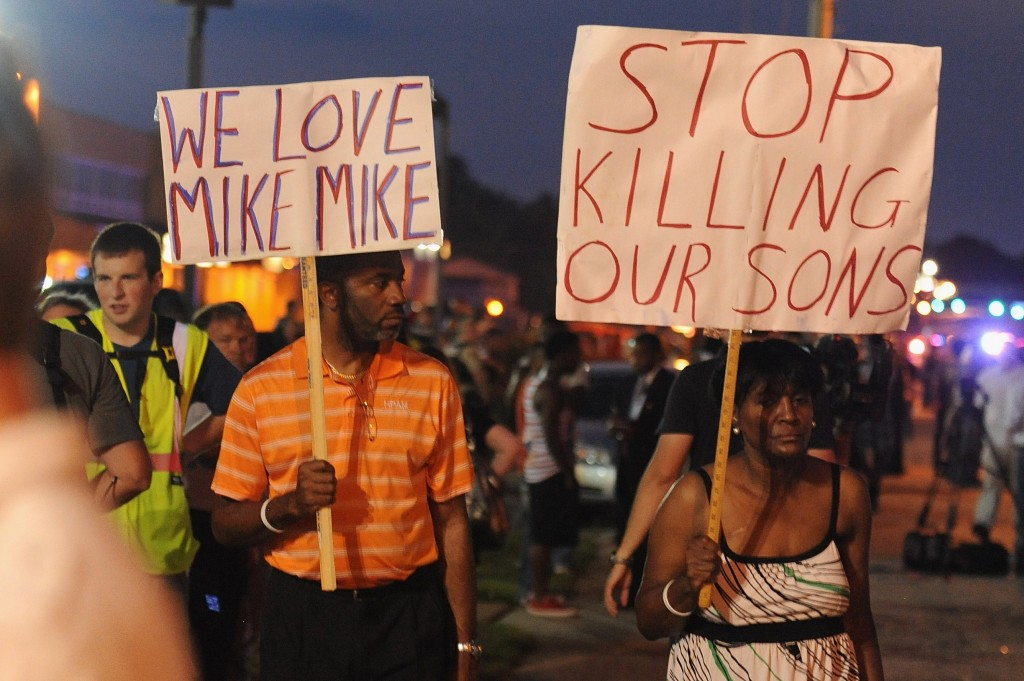 Demonstrators display signs during a protest in Ferguson, Missouri Monday night. Photo by Michael B. Thomas/AFP/Getty Images