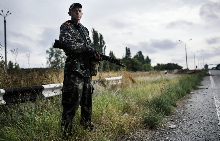 A pro-Russia militant stands guard on a road near Donetsk, on August 18, 2014. Photo by Dimitar Kilkoff/Getty Images