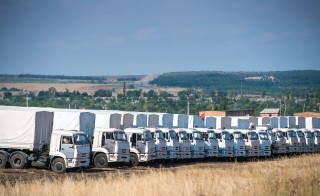 Trucks part of a Russian humanitarian convoy are parked near a checkpoint at the Ukrainian border in the Rostov region on Aug. 20. Photo by Dmitry Serebryakov/AFP/Getty Images