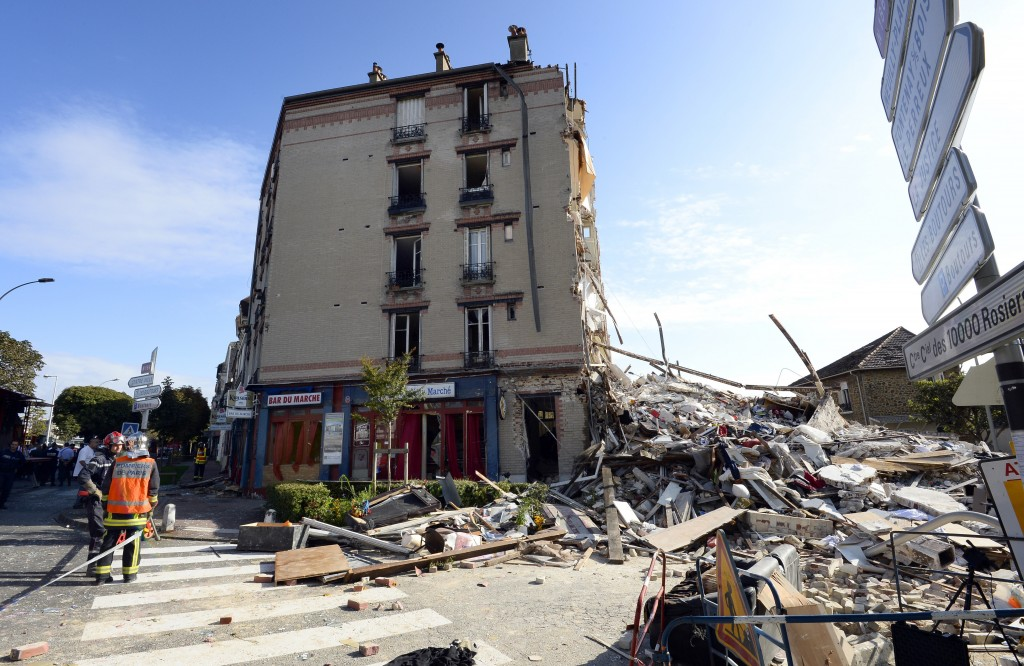 Firefighters search through the rubble of a four-storey residential building that collapsed following a blast in Rosny-sous-Bois in the eastern suburbs of Paris on August 31, 2014. A four-storey residential building collapsed in a Paris suburb following an explosion possibly due to a gas leak, killing at least one child and an elderly woman, local emergency services said. Ten people were also wounded, including four in serious condition, while 11 others are still unaccounted for. AFP PHOTO / BERTRAND GUAY (Photo credit should read BERTRAND GUAY/AFP/Getty Images)
