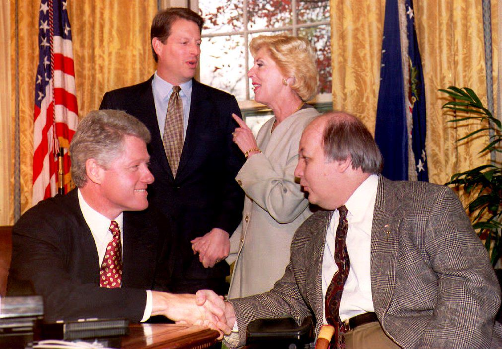 U.S. President Bill Clinton (L) congratulates former Reagan Administration Press Secretary James Brady (R) on the passage of the Brady bill as Vice President Al Gore (2nd-L) and Sarah Brady look on during a meeting at the White House 24 November 1993. Photo credit should read JENNIFER YOUNG/AFP/Getty Images