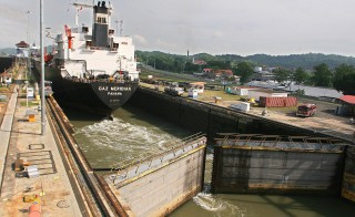 "A tanker crosses through the Panama Canal's Miraflores locks on April 21, 2006. The size of the locks, which are 110 feet wide, limits the size of ships that can pass through. The allowable size is known as ""Panamax."" The tolls for container ships to cross are about $50,000 to $250,000, cruise ships $80,000 to $300,000, and yachts and other small vessels $1,300 to $2,500. Photo by Teresita Chavarria/AFP/Getty Images"