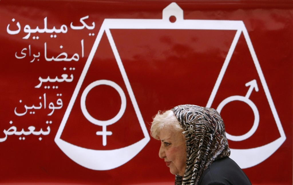 "Iranian poet and women rights activist Simin Behbahani walks past a banner reading ""one million signatures to change the biased laws"" and bearing a scale balancing female and male symbols during a press conference in Tehran. Photo by Behrouz Mehri/AFP/Getty Images)"