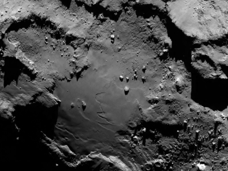 "A close-up shows craters, steep cliffs and the smooth region on the ""base"" of the ""body"" section of comet 67P/Churyumov-Gerasimenko. The image was taken by Rosetta about 81 miles away on Aug. 6. Photo courtesy of the European Space Agency"