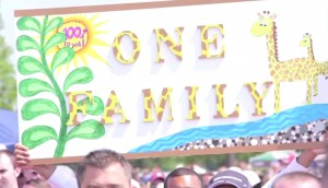 "Protesters at a Market Basket rally hold a sign saying ""One Family,"" featuring giraffes, the mascot they've adopted. NewsHour still image."