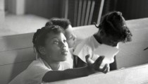 Three young African-American girls sitting together during a Freedom School class at Mt. Zion Baptist Church in Hattiesburg, Mississippi, during Freedom Summer 1964.  Photo by Herbert Randall from Herbert Randall Freedom Summer Photographs collection, McCain Library and Archives, The University Southern Mississippi.