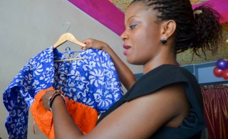 Patrice Juah hangs a dress in her store, Moie, in Monrovia, Liberia. Photo courtesy of Juah