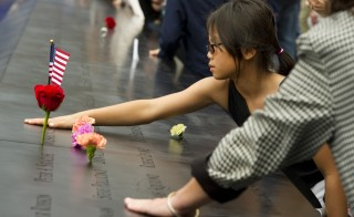 A young girl touches a name on the 9/11 memorial South Tower pool of the World Trade Center September 11, 2011 in New York as the US marks 10 years since the 9/11 attacks. AFP PHOTO/DON EMMERT (Photo credit should read DON EMMERT/AFP/Getty Images)