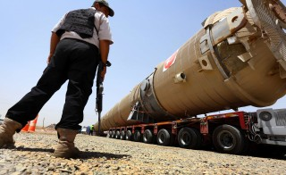 A section of an oil refinery is guarded as it is brought on a truck to the Kawergosk Refinery, east of the city of Irbil in northern Iraq on July 14. An offensive by jihadists had cut output by 260,000 barrels a day in June to 3.17 million, after fighting forced the closure of the country's biggest refinery and slashed production from the giant Kirkuk field, according to a report from the International Energy Agency. Photo by Safin Hamed/AFP/Getty Images
