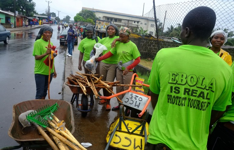 City workers wear green t-shirts warning of Ebola as they prepare to clean the streets in the centre of the Liberian capital Monrovia on September 6, 2014. Photo by  Dominique Faget/AFP/Getty Images