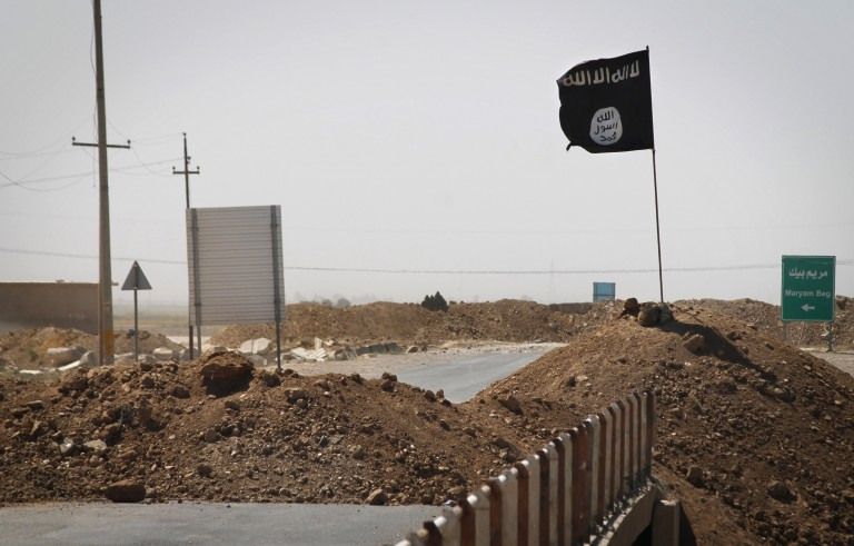 A flag of the Islamic State  is seen on the other side of a bridge at the frontline of fighting between Kurdish Peshmerga fighters and Islamist militants in Rashad, on the road between Kirkuk and Tikrit, on Sept. 11. Photo by Jm Lopez/AFP/Getty Images
