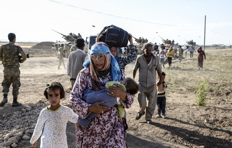 Syrian Kurds walk by Turkish soliders after crossing into Turkey near the southeastern town of Suruc in Sanliurfa province, on September 19, 2014. Several thousand Syrian Kurds began crossing into Turkey on Friday fleeing Islamic State fighters who advanced into their villages, prompting warnings of massacres from Kurdish leaders. AFP PHOTO/ILYAS AKENGIN (Photo credit should read ILYAS AKENGIN/AFP/Getty Images)