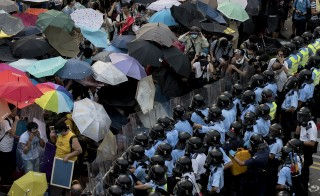 Pro-democracy protesters hold umbrellas and wear protective clothing in front of a police line near the government headquarters in Hong Kong on September 28, 2014. Police fired tear gas as tens of thousands of pro-democracy demonstrators brought parts of central Hong Kong to a standstill Sunday, in a dramatic escalation of protests that have gripped the semi-autonomous Chinese city for days. AFP PHOTO / ALEX OGLE