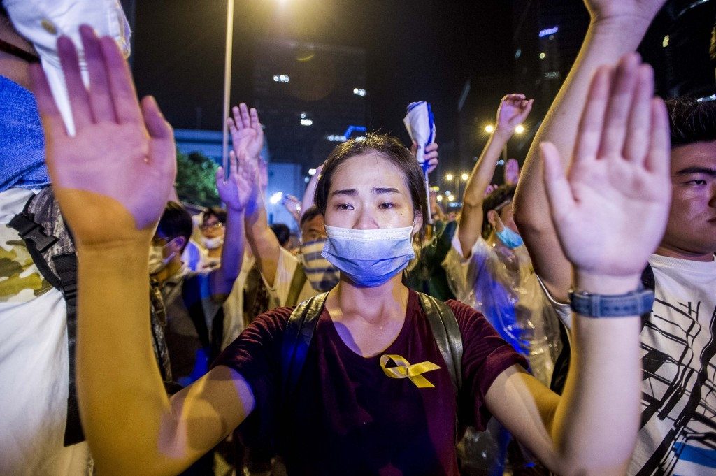 A demonstrator gestures opposite policemen during a pro-democracy protest in Hong Kong on September 28, 2014. Police fired tear gas as tens of thousands of pro-democracy demonstrators brought parts of central Hong Kong to a standstill in a dramatic escalation of protests that have gripped the semi-autonomous Chinese city for days. AFP PHOTO / XAUME OLLEROS        (Photo credit should read XAUME OLLEROS/AFP/Getty Images)