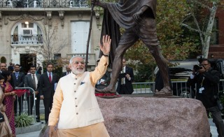 Indian Prime Minister Narendra Modi waves to supporters after paying his respects at a statue of Mahatma Gandhi in front of the Indian embassy in Washington on September 30, 2014. Modi met September 29 with US President Barack Obama, Vice President Joe Biden and other key US officials at the White House for a private dinner, ahead of formal talks in the Oval Office on Tuesday. Photo by Nicholas Kamm/AFP/Getty Images