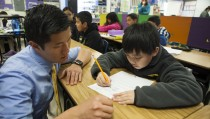 Fifth grade science and math teacher Stephen Pham helps a student at Rocketship SI Se Puede, a charter, public elementary school, on February 18, 2014 in San Jose, California. (Photo by Melanie Stetson Freeman/The Christian Science Monitor
