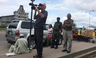Tom Adair and Fred de Sam Lazaro, near a police security guard on the streets of Port Harcourt, Nigeria. Photo by Nikki See