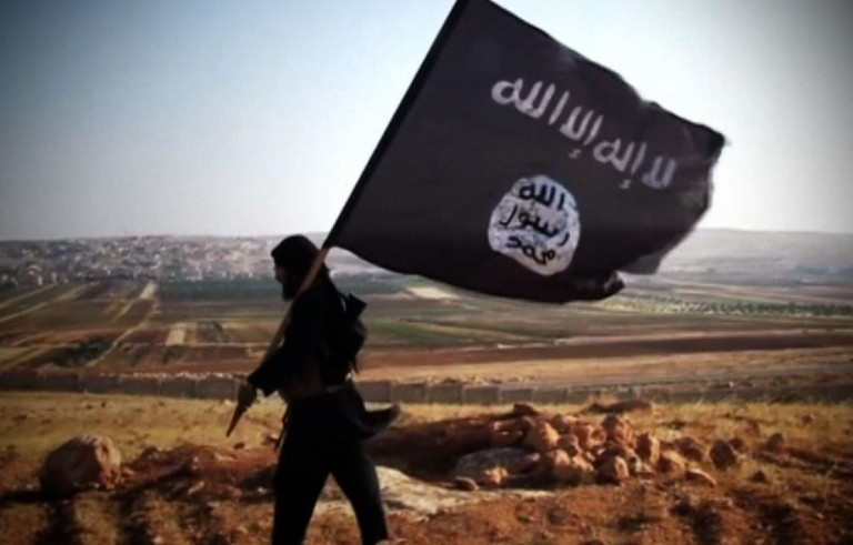 A fighter of the Islamic State group carries their flag. Screen grab from PBS NewsHour.